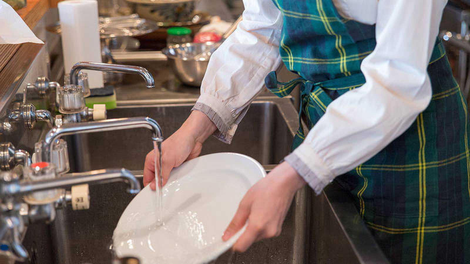 Una empleada friega los platos en un resturante