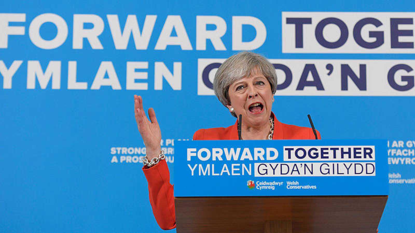 Theresa May rectifica algunas medidas de su programa durante un acto de campaña en Gales.