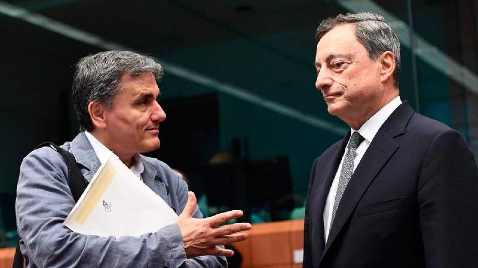 El ministro de Finanzas griego Euclid Tsakalotos habla con el presidente del Banco Central Europeo Mario Draghi