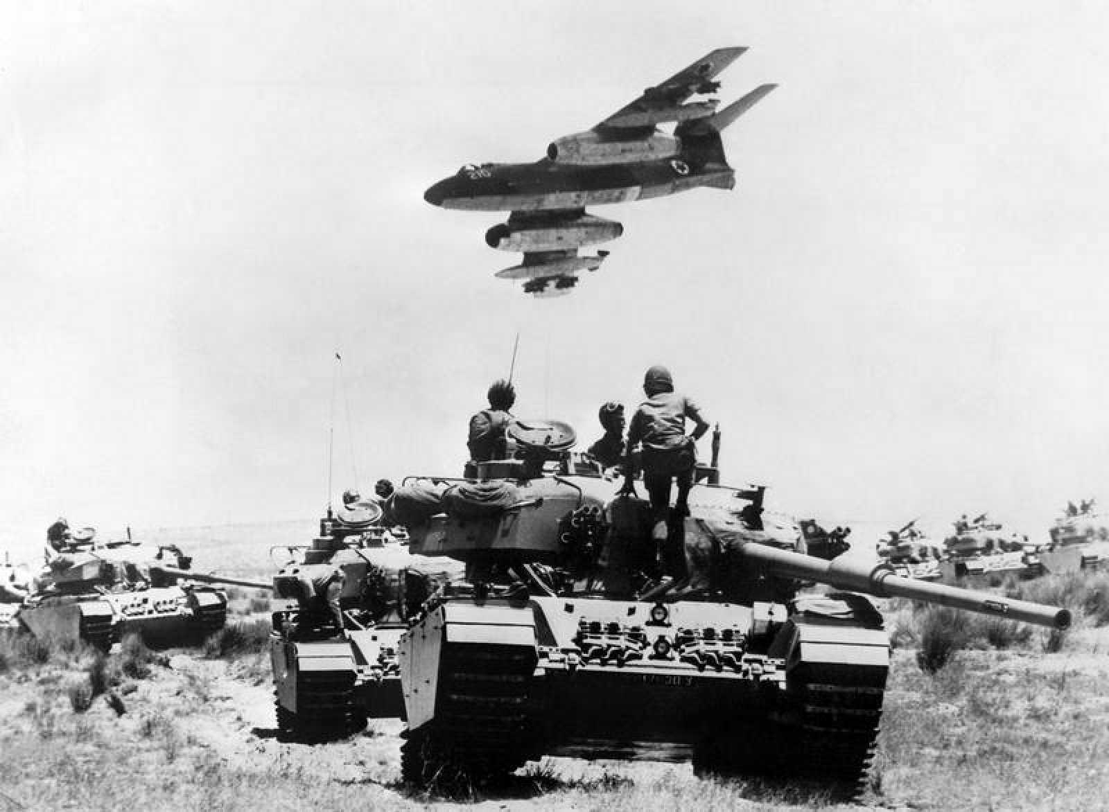 Un avión de guerra sobrevuela las tropas israelíes que avanzan en tanques por la península del Sinaí en la frontera entre Israel y Egipto, el 25 de mayo de 1967.