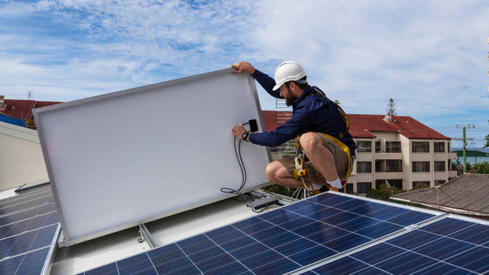 Un operario coloca placas solares en el tejado de un edificio
