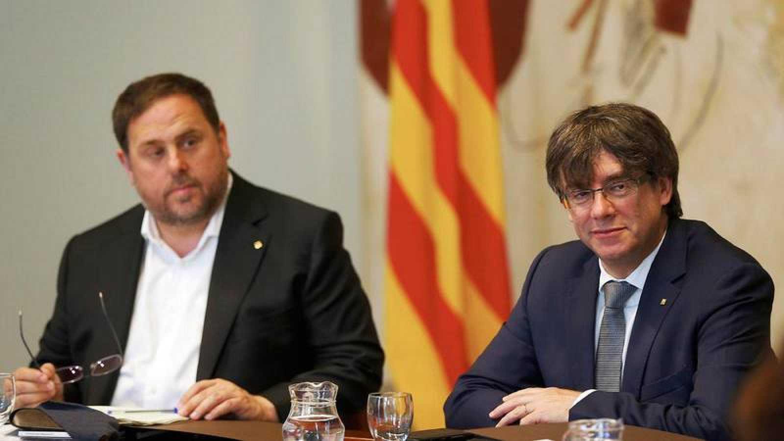 El presidente de la Generalitat catalana, Carles Puigdemont, y su vicepresidente, Oriol Junqueras (i).
