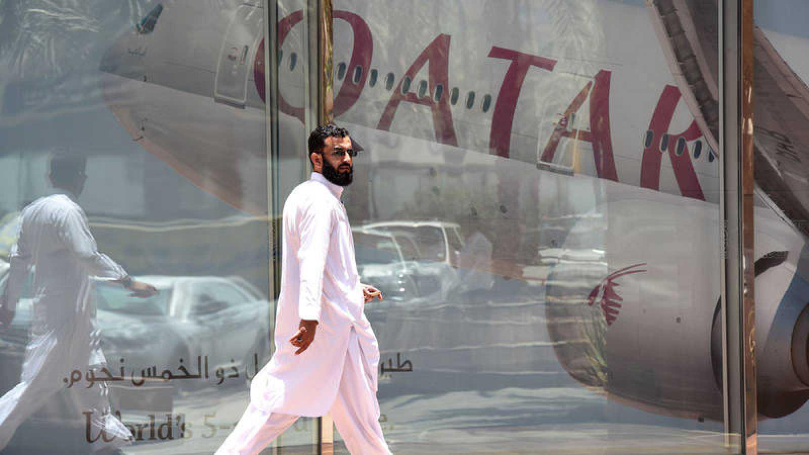 Un hombre camina delante de un avión de Qatar Airways en la capital saudí, Rihad.
