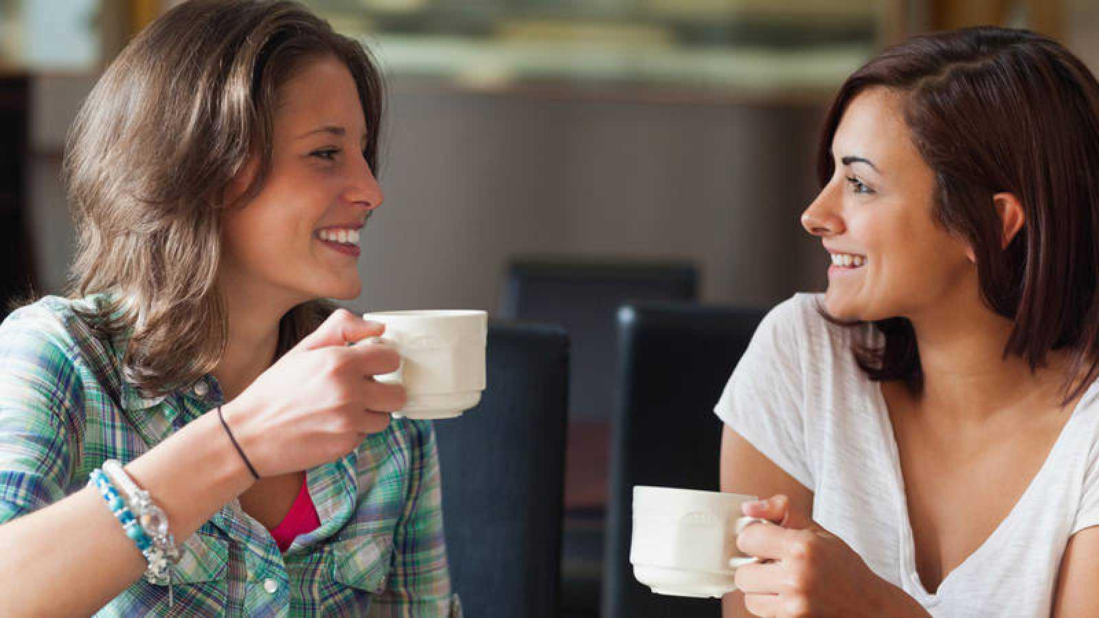 Dos chicas jóvenes conversan mientras toman un café