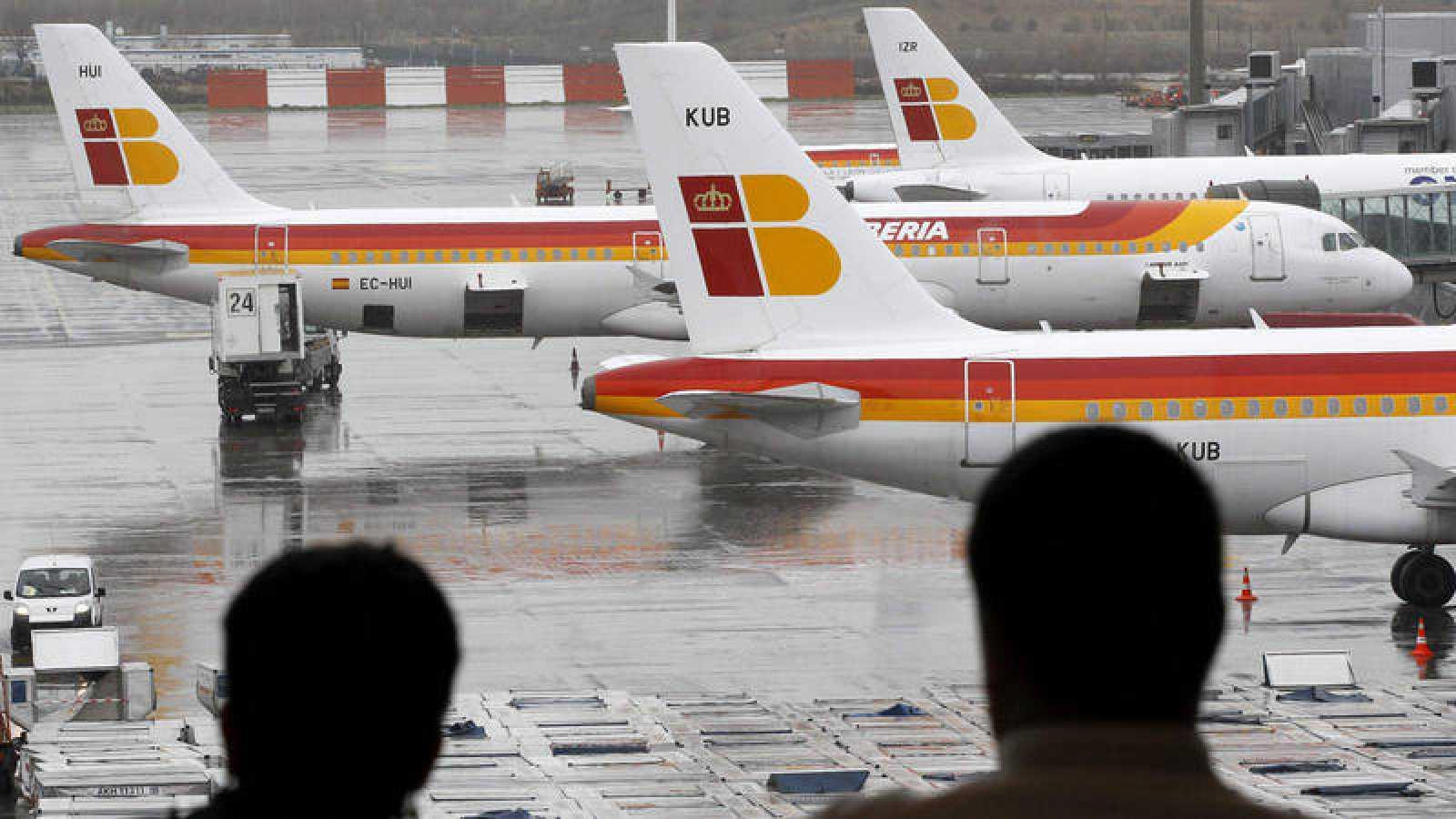 Dos pasajeros observan aviones de Iberia en Barajas en una imagen de archivo