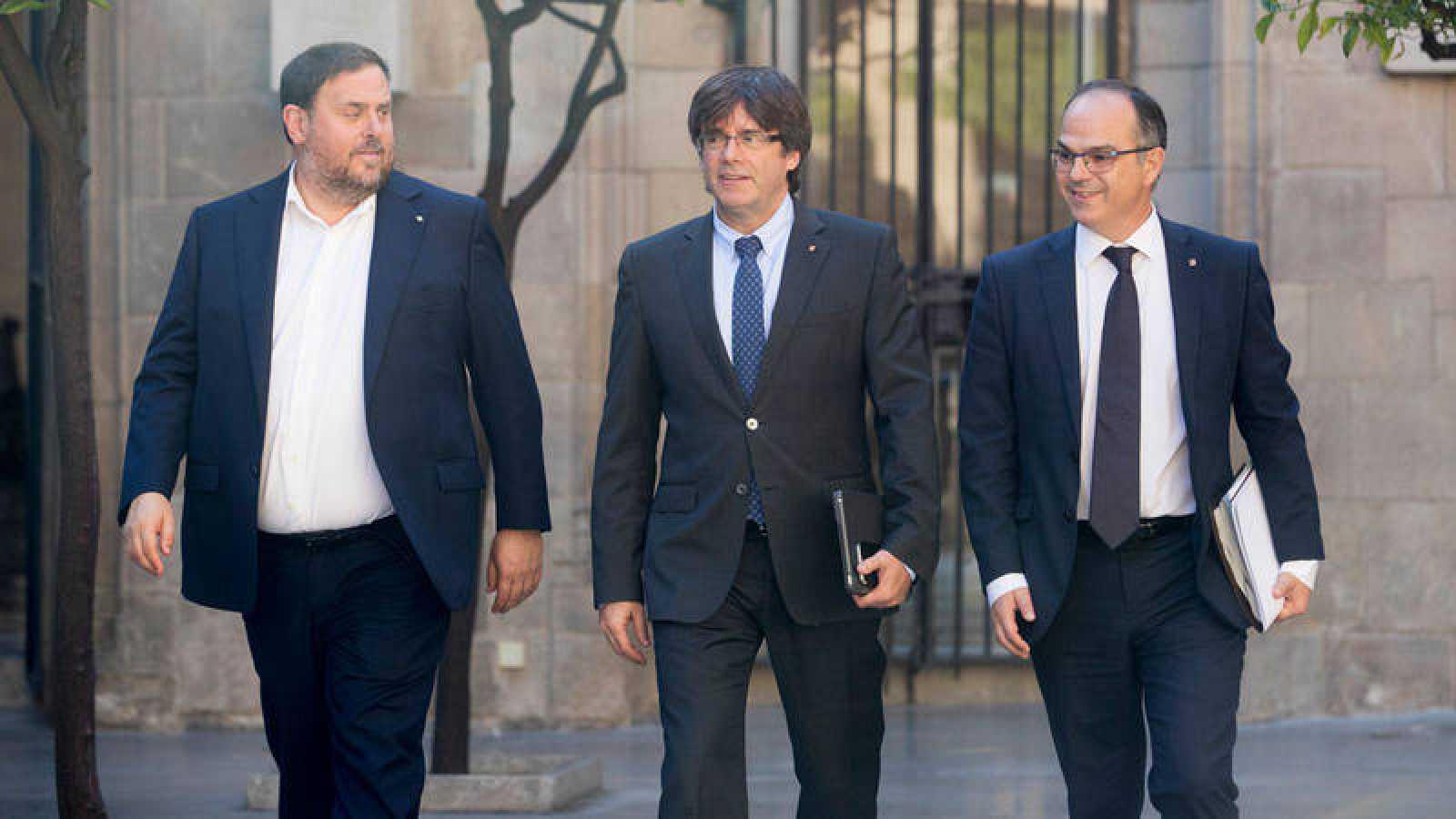 El presidente de la Generalitat, Carles Puigdemont junto al vicepresidente y conseller de Economía, Oriol Junqueras  y el conseller de la Presidencia, Jordi Turull (d)