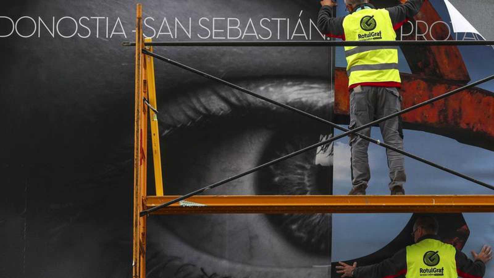 2674d5e3794e Operarios colocan uno de los carteles del Festival Internacional de Cine de San  Sebastián.