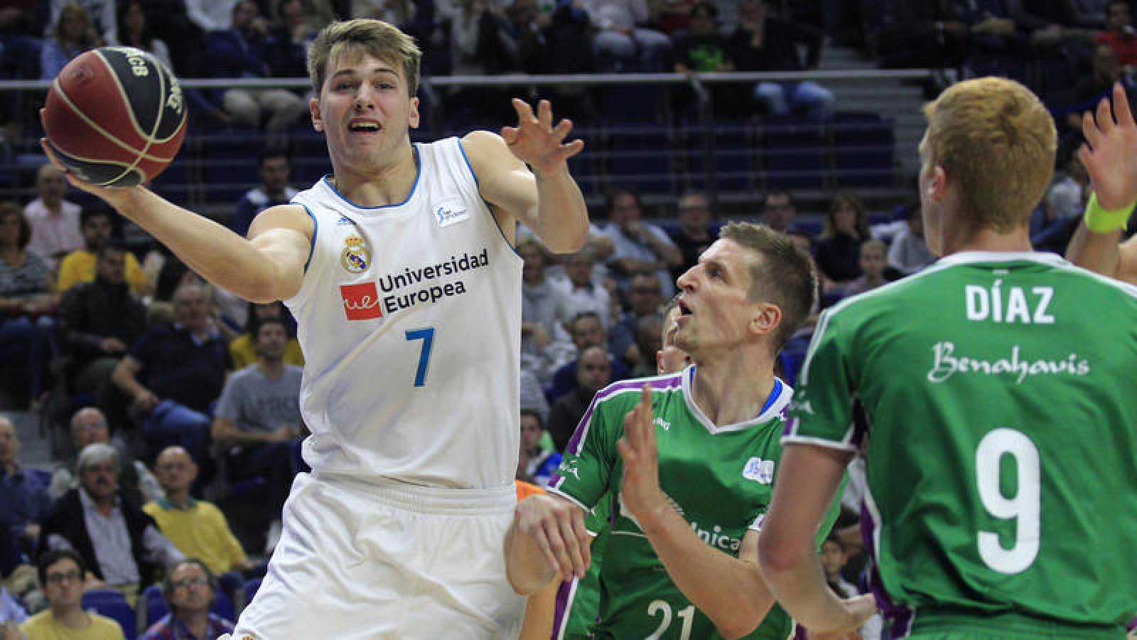 El base esloveno del Real Madrid Luka Doncic (i) intenta avanzar ante el alero polaco del Unicaja Adam Waczynski (2i).