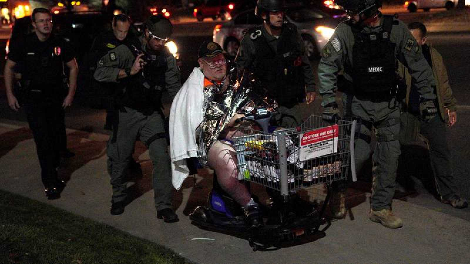 Un hombre es evacuado del supermercado por agentes de los SWAT