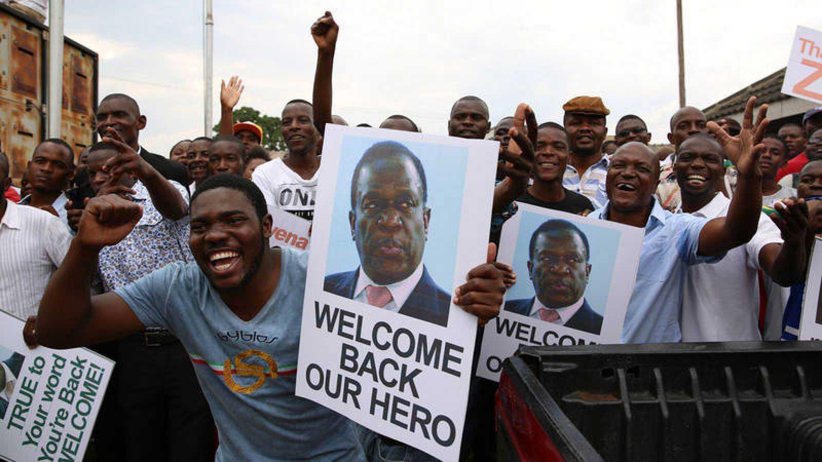 Decenas de zimbabuenses celebran con pancartas la llegada del exvicepresidente