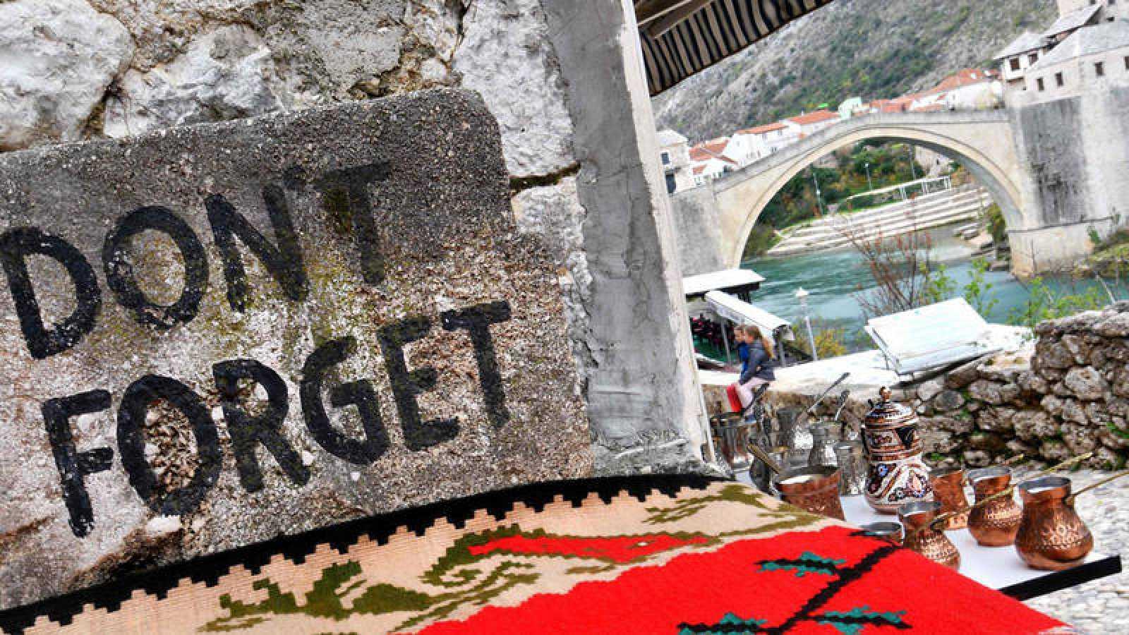 """Un cartel en la ciudad bosnia de Mostar con la frase en inglés """"No olvidar"""". Al fondo, el Puente Viejo de la ciudad, destruido por los croatas durante la guerra civil y reconstruido por fuerzas españolas."""