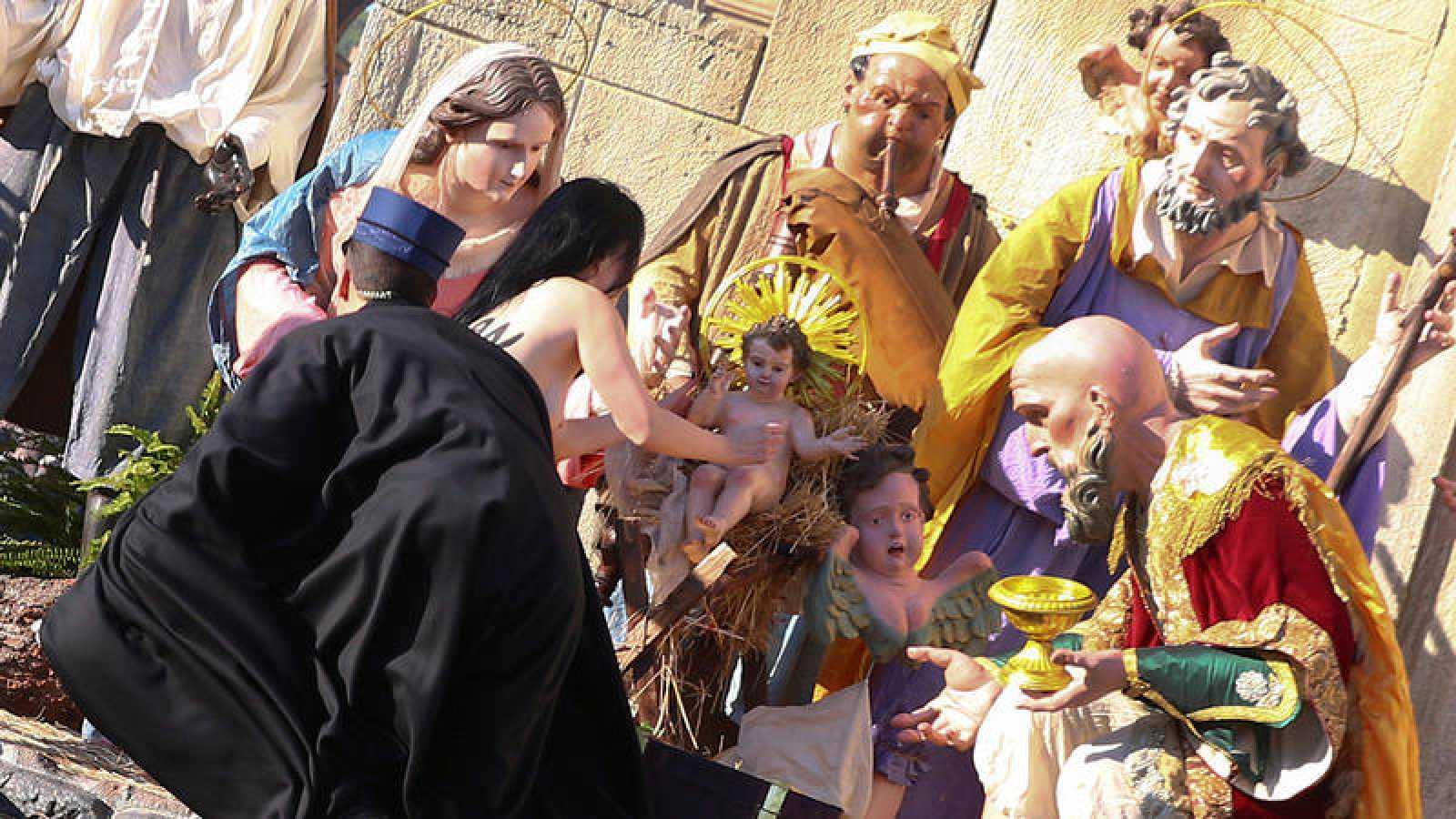 Una activista de Femen intenta llevarse la figura del niño Jesus del belén del Vaticano el diá de Navidad