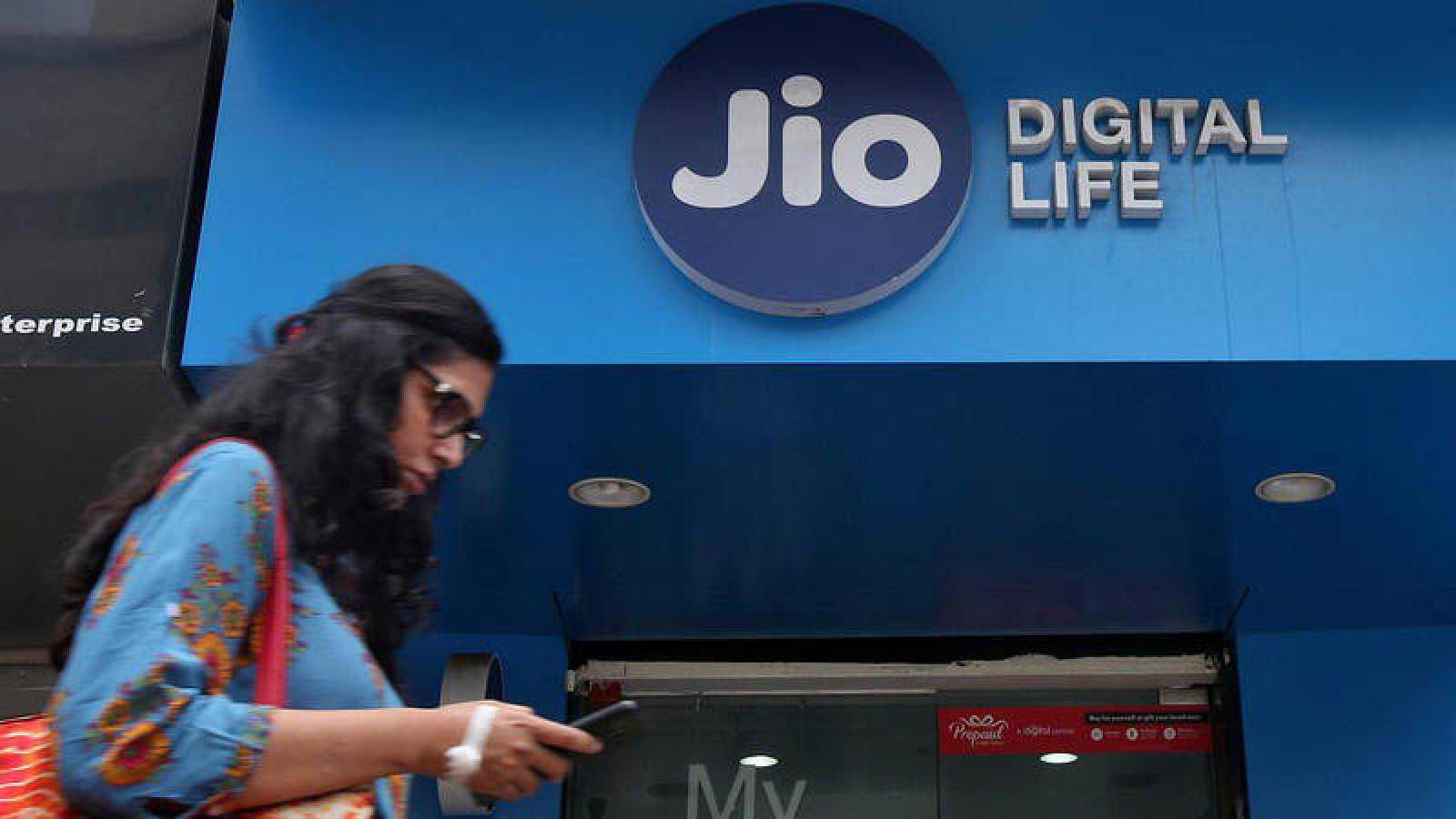 Una mujer pasa por delante de una tienda de la compañía telefónica Jio, en India.
