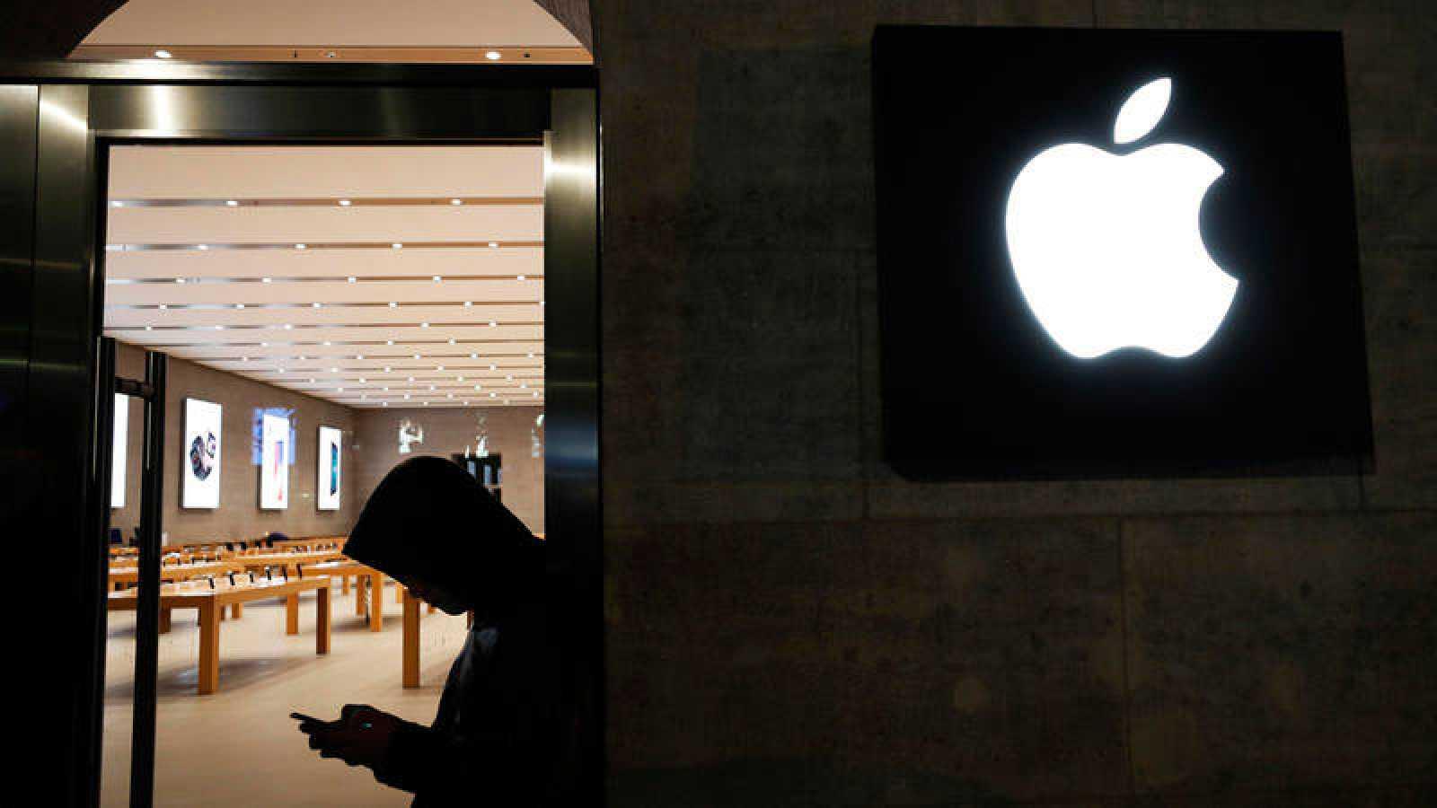 Un cliente mira su dispositivo móvil frente a una tienda Apple.