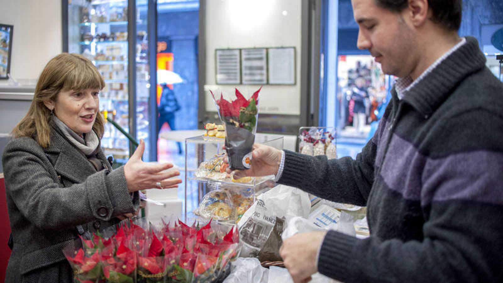Una mujer recibe una flor de Pascua en un comercio de Bilbao