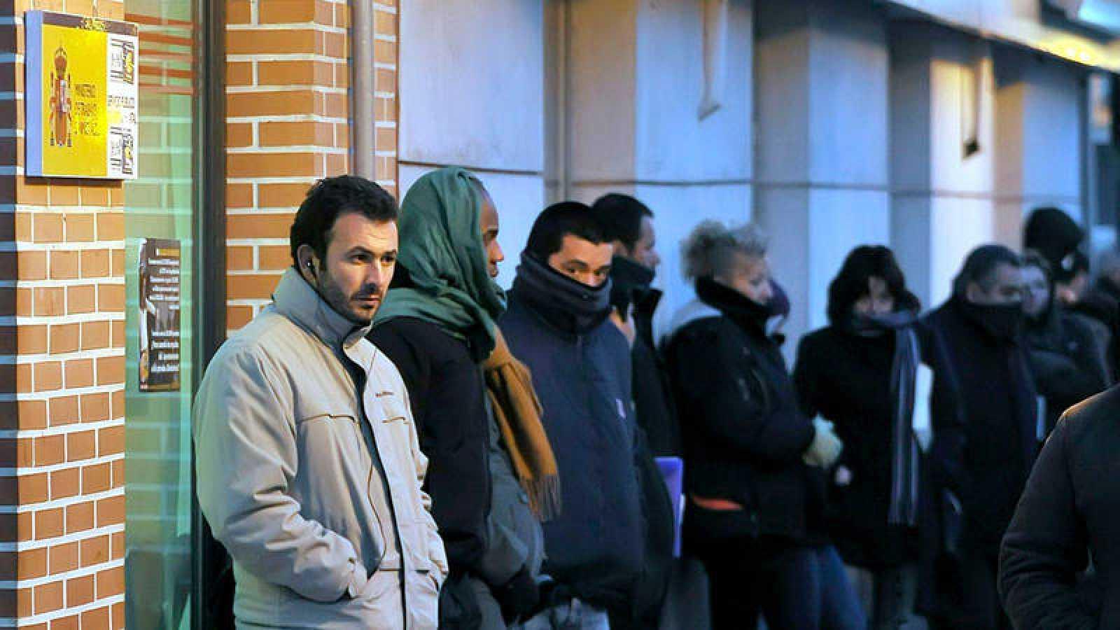 Varias personas hacen cola ante una oficina de empleo en Alcalá de Henares