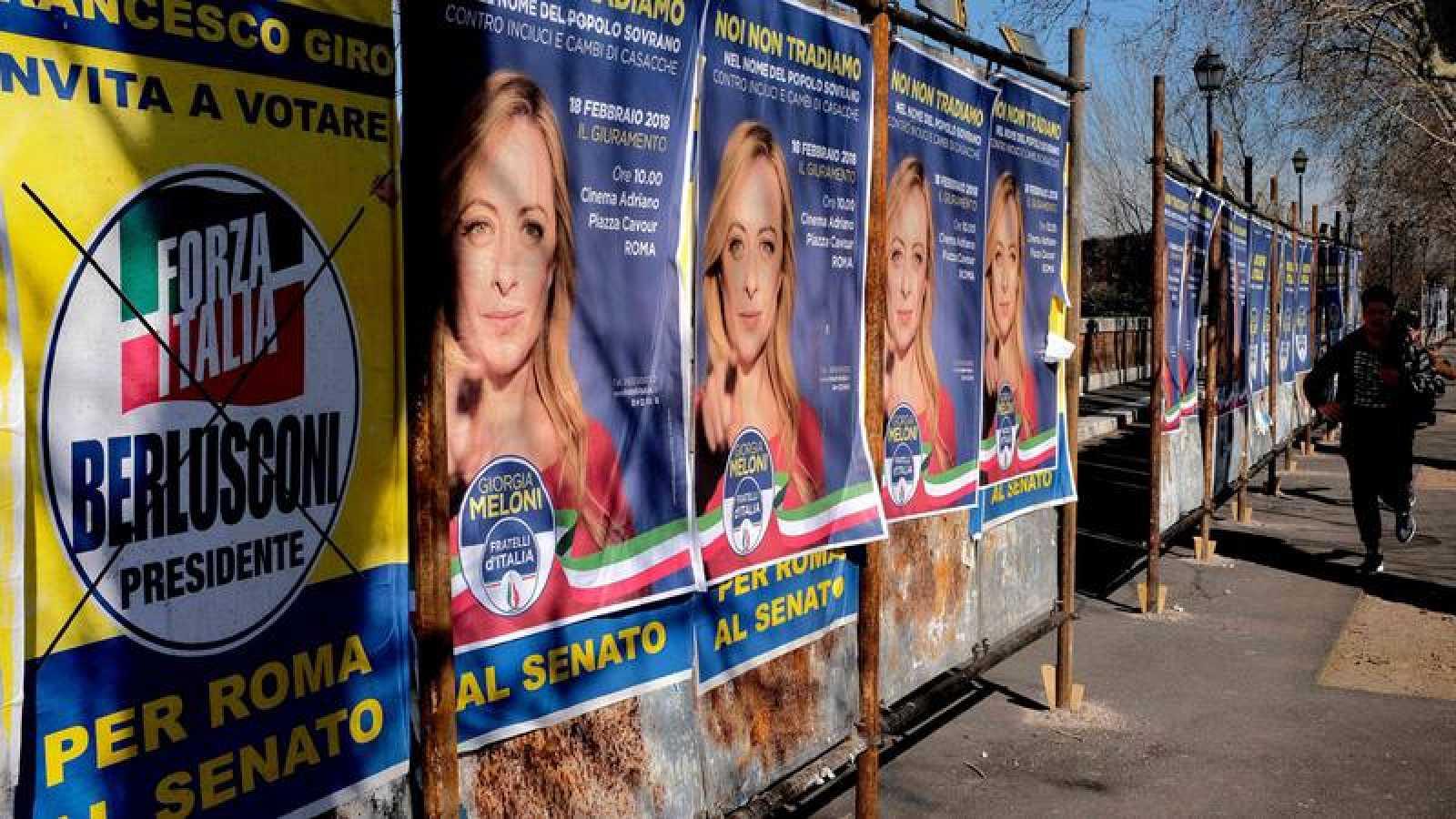 Un hombre pasea por una calle con carteles electorales en Roma