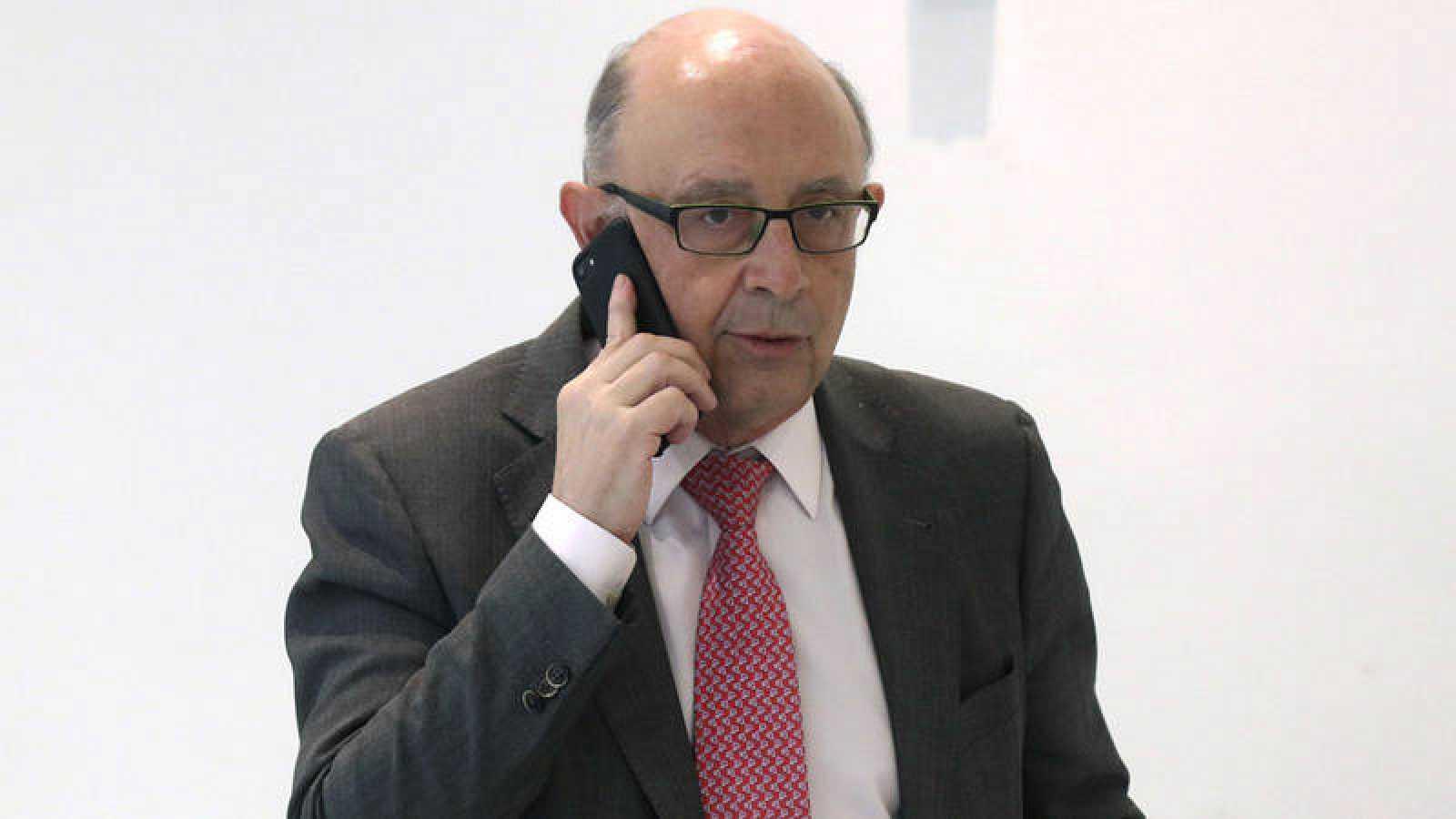 El ministro de Hacienda habla por el móvil