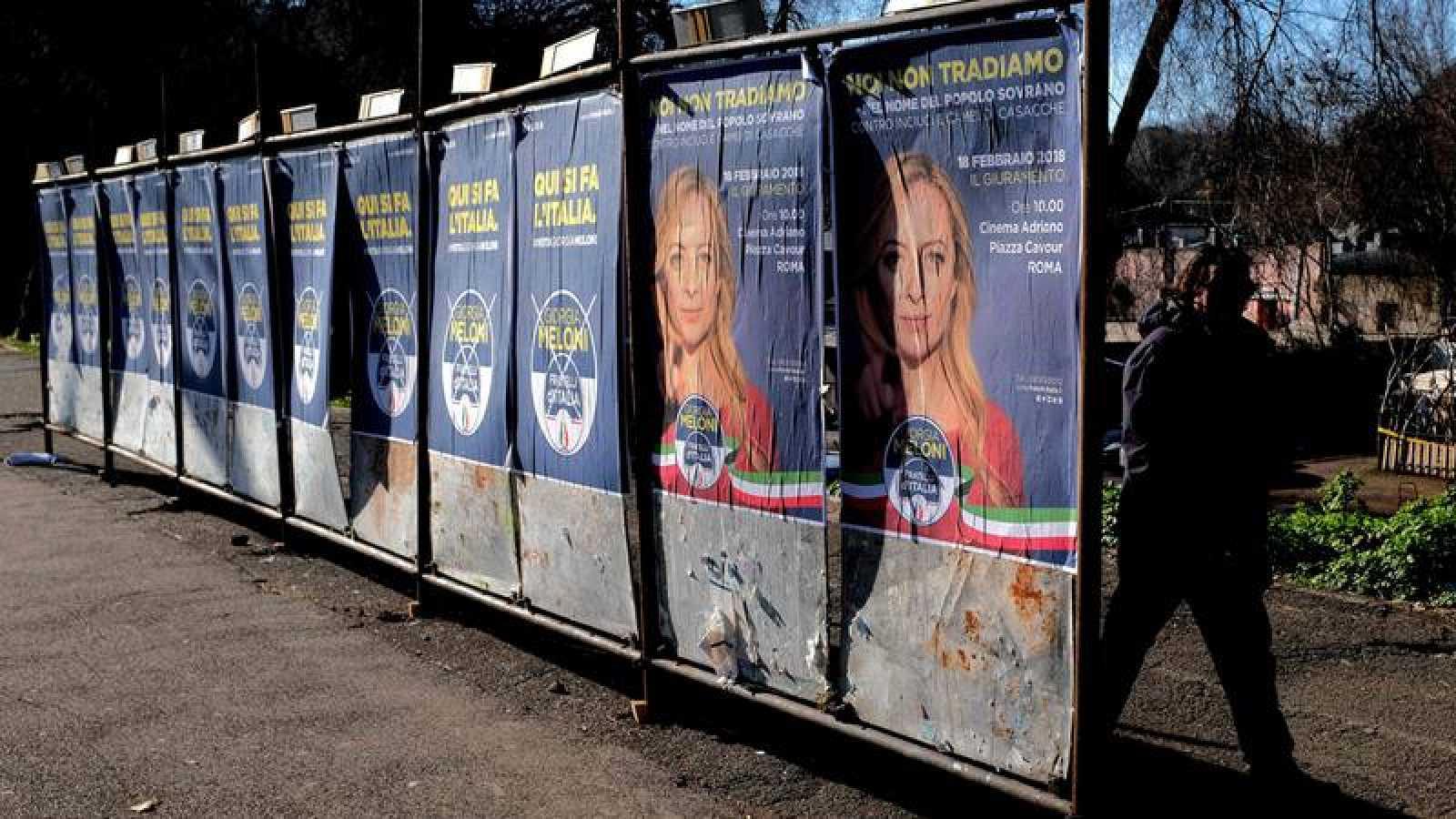 Un hombre pasea frente a los carteles electorales en Roma