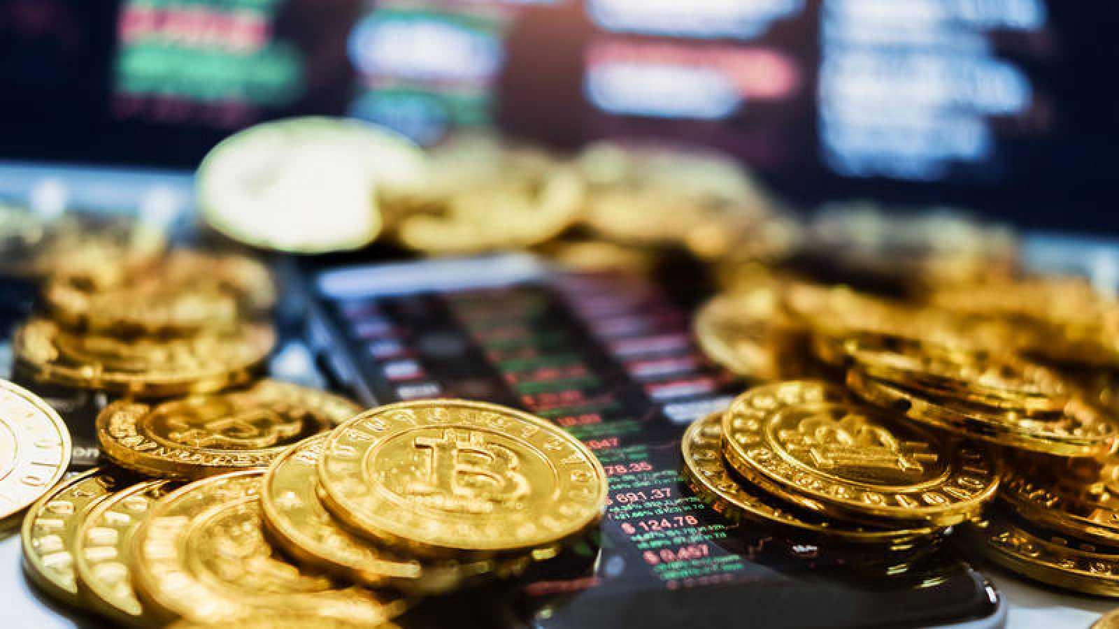 Monedas representando bitcoins junto a un móvil con datos bursátiles