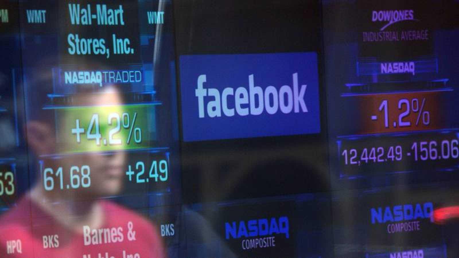 El logo de Facebook se vislumbra a traves de las ventanas del cambiador del Nasdaq