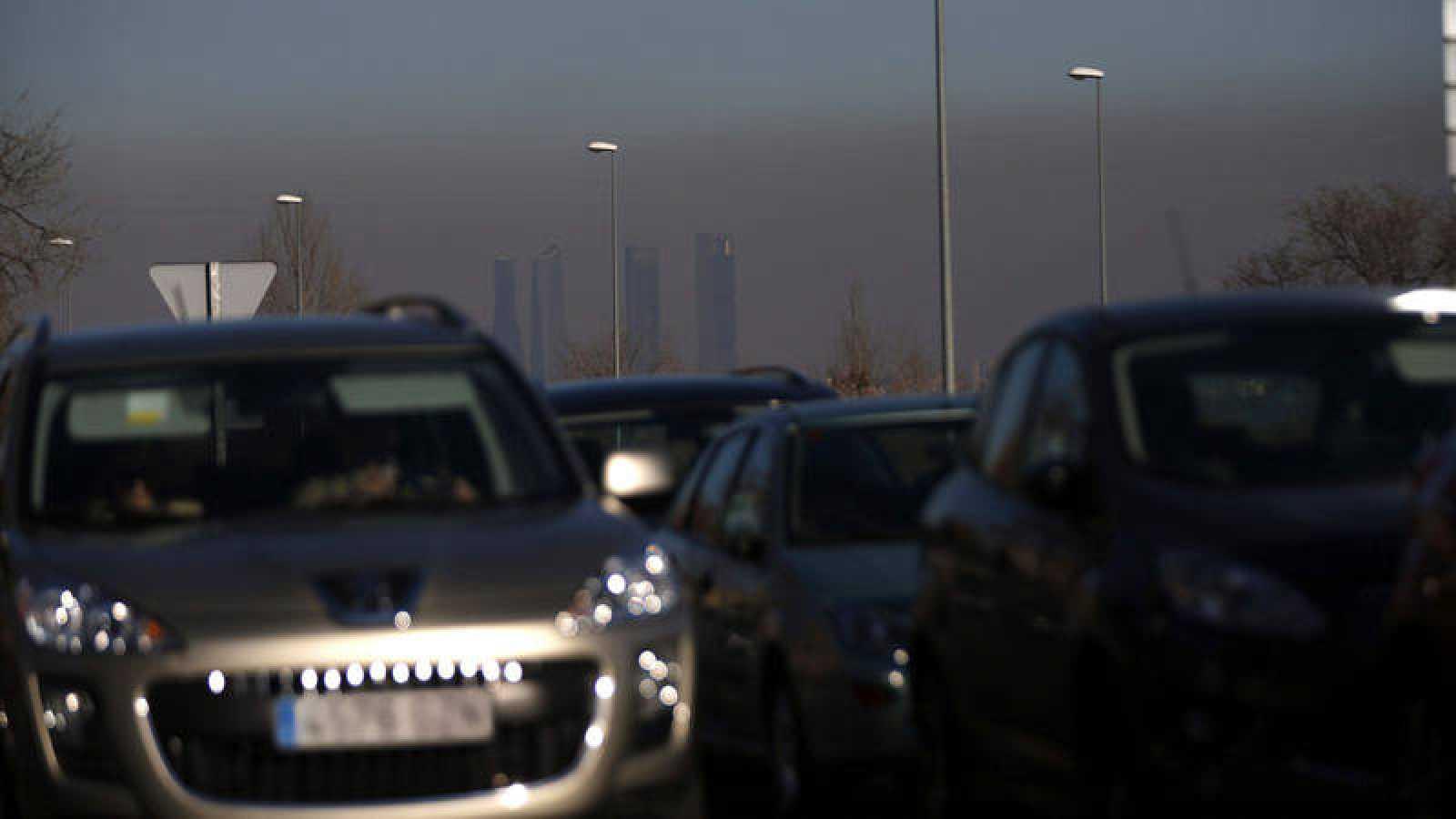 Tráfico en las carreteras que rodean Madrid con el fondo de la nube de contaminación que cubre la capital española
