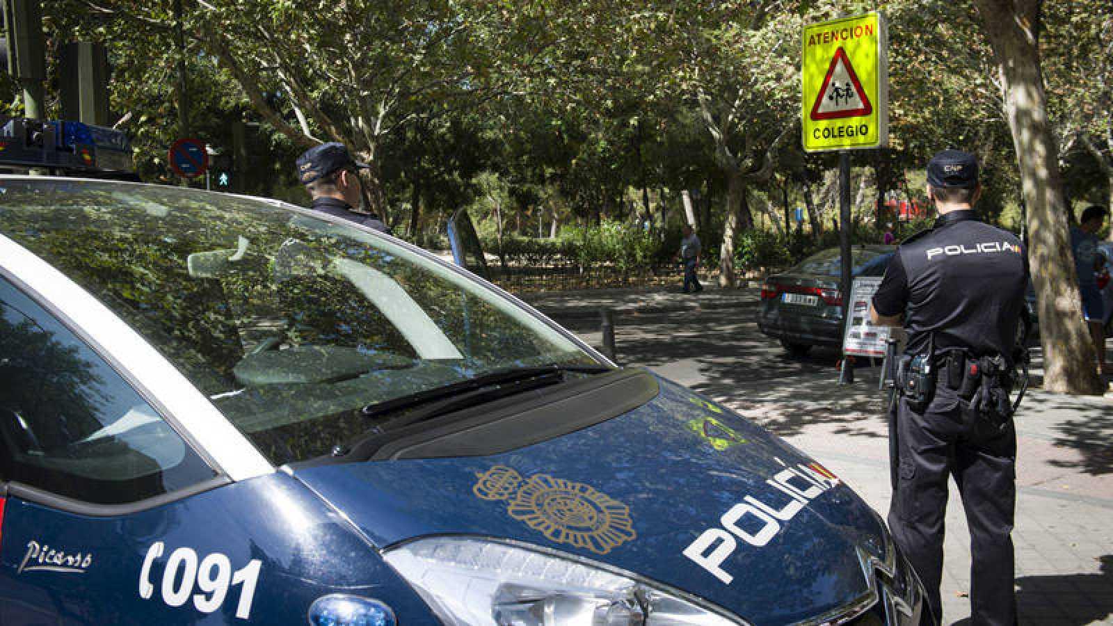 Fotografía de archivo de la Policía vigilando la salida de un colegio en Madrid en 2014