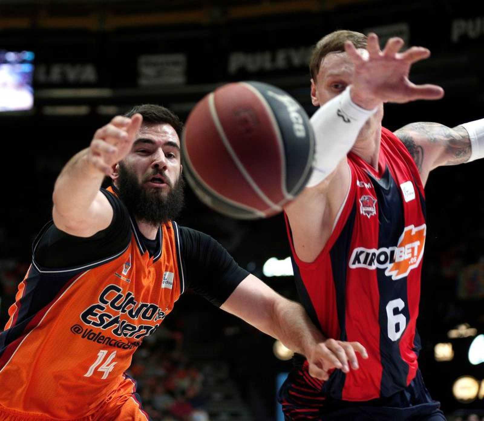 El pívot montenegrino del Valencia Basket Bojan Dubljevic (i) lucha un balón con el letón Janis Timma, del Baskonia, durante el partido.