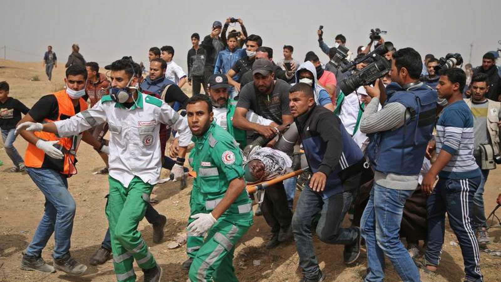 Paramédicos palestinos asisten a una herida durante un enfrentamiento con el Ejército israelí en Gaza