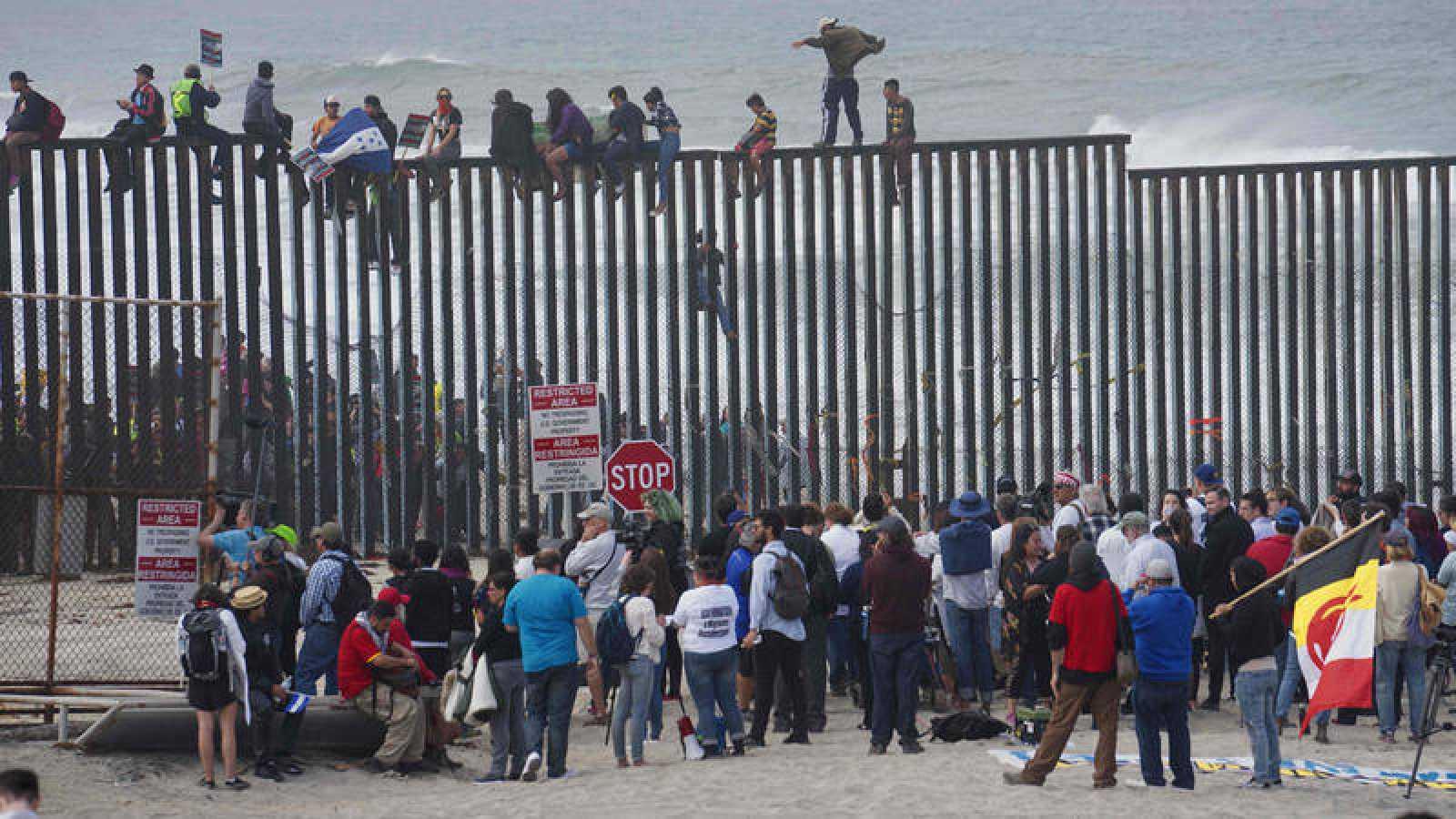Migrantes centroamericanos escalan la valla fronteriza con EE.UU. en San Isidro, California
