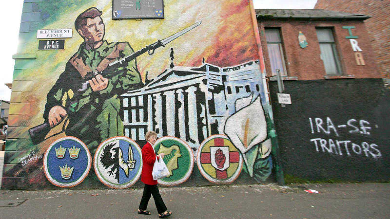 """Una mujer pasa ante un mural nacionalista en Belfast, junto a una pintada que califica de """"traidores"""" al IRA y al Sinn Féin"""