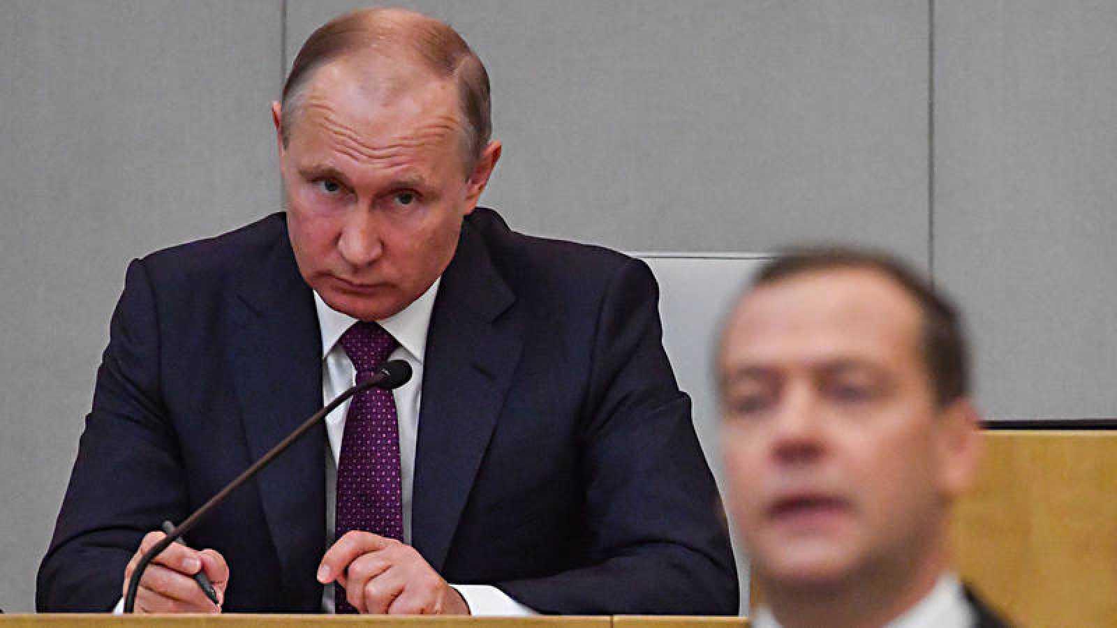 El presidente ruso, Vladímir Putin, escucha al primer ministro, Dimitri Medvedev, durante la sesión parlamentaria que ha renovado el mandato de este