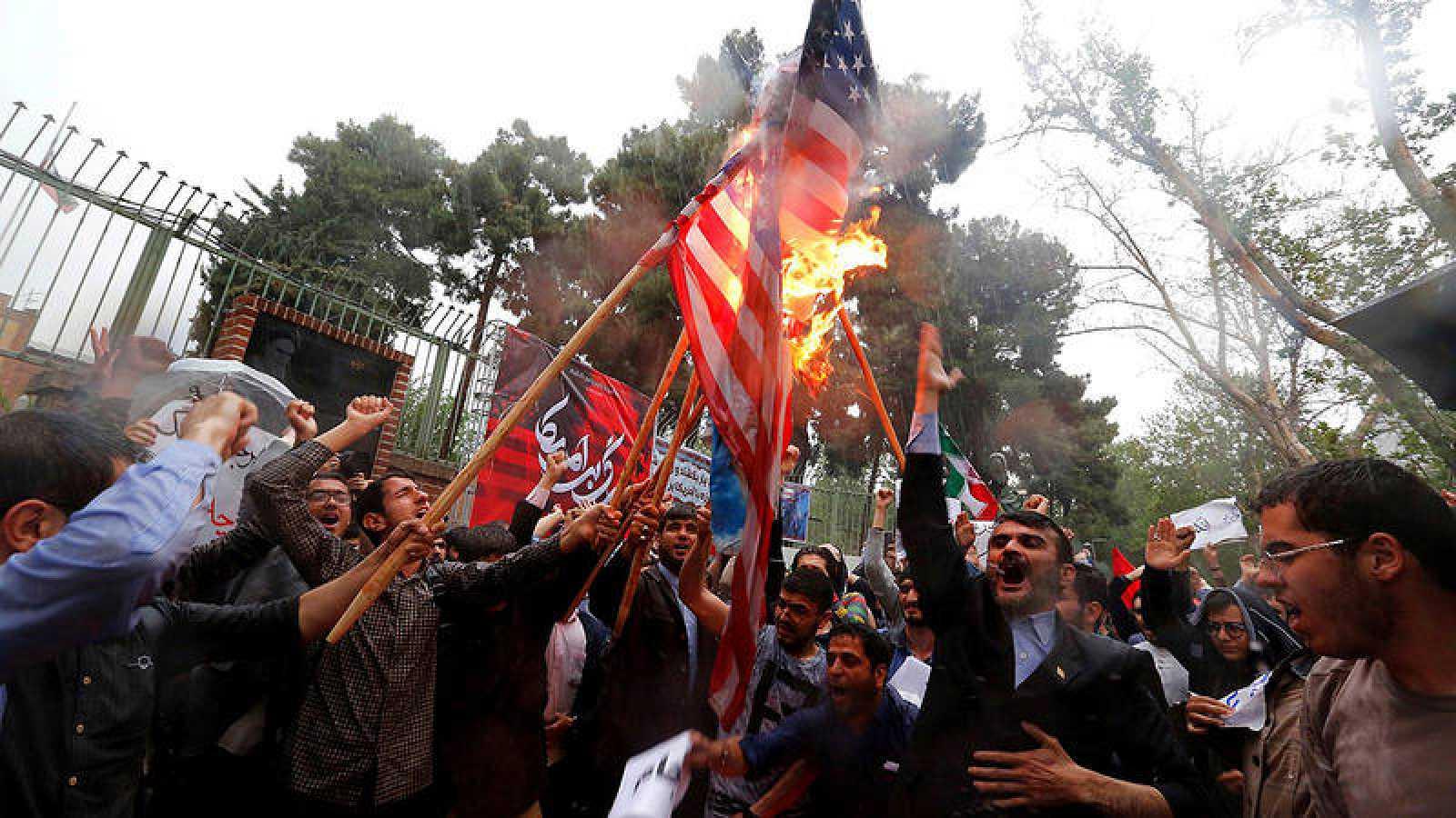 Un grupo de iraníes quema una bandera estadounidense frente a la antigua embajada estadounidense en Teherán
