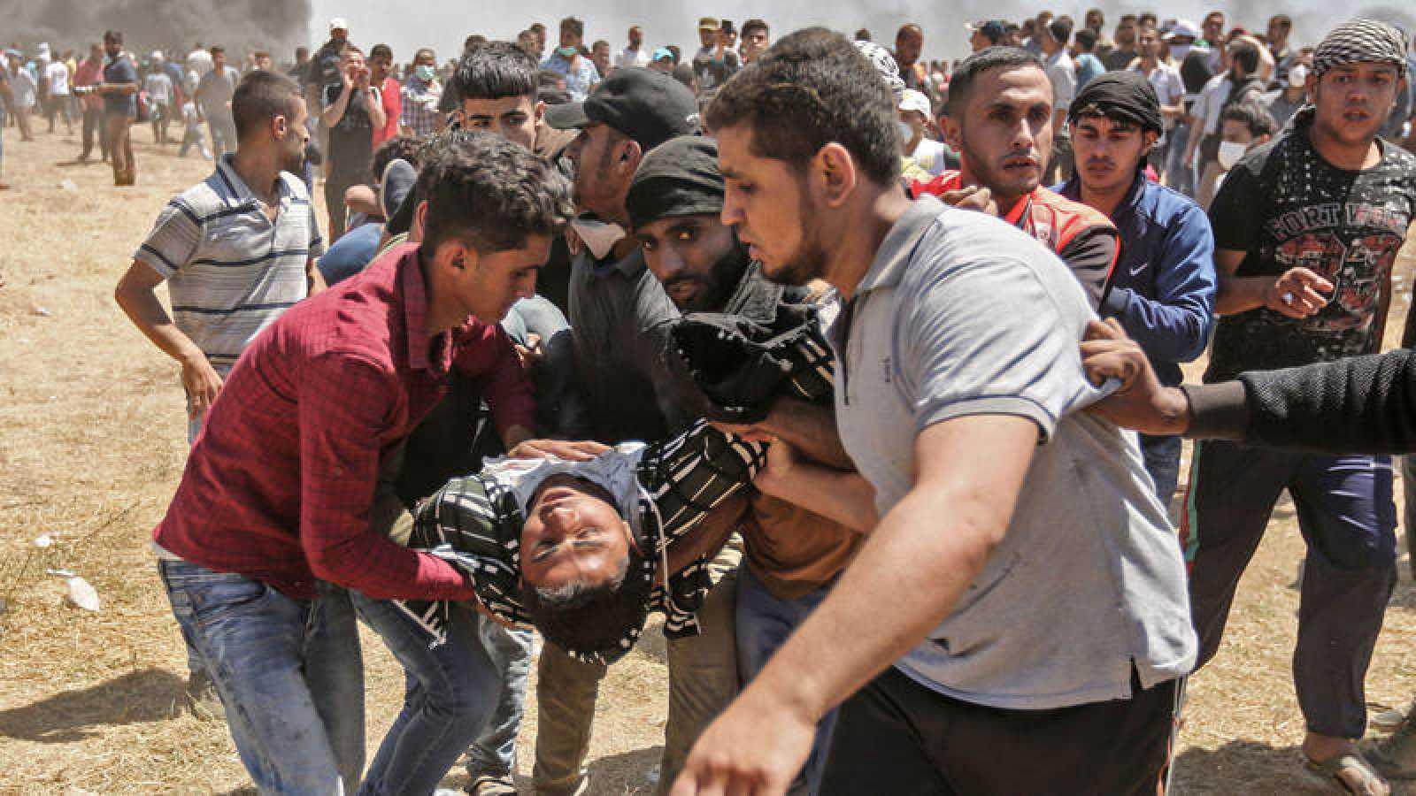 Palestinos llevan a un hombre herido en las protestas del pasado lunes 14 de mayo en Gaza