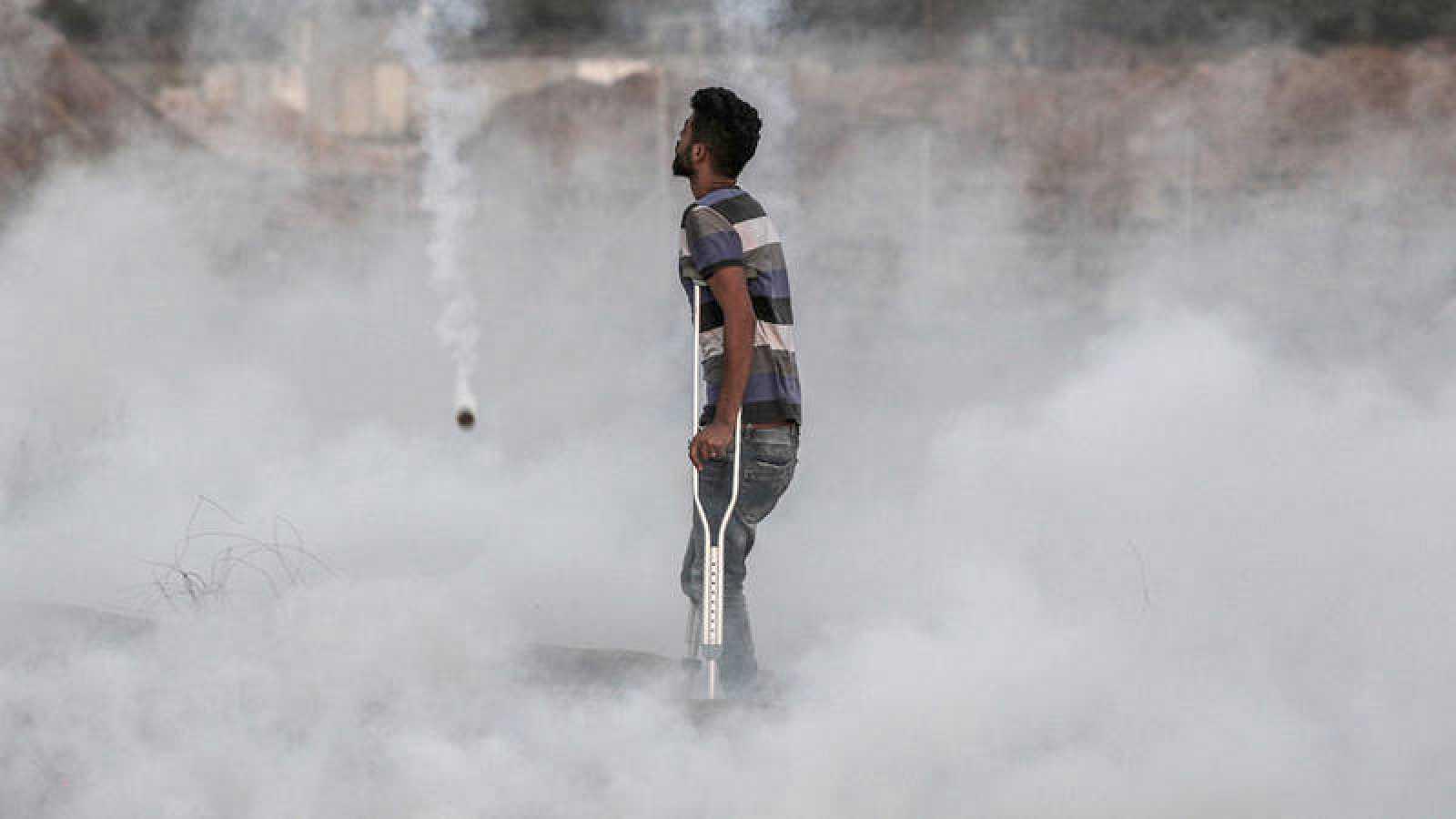 Un palestino herido entre los gases lacrimógenos lanzados por el Ejército israelí en la frontera con Gaza