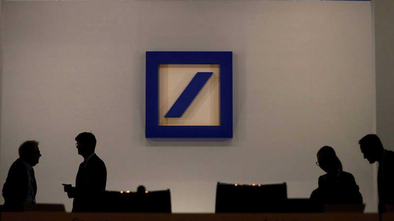 Siluetas de varios empleados del Deutsche Bank perfiladas sobre un fondo con el logo de la entidad