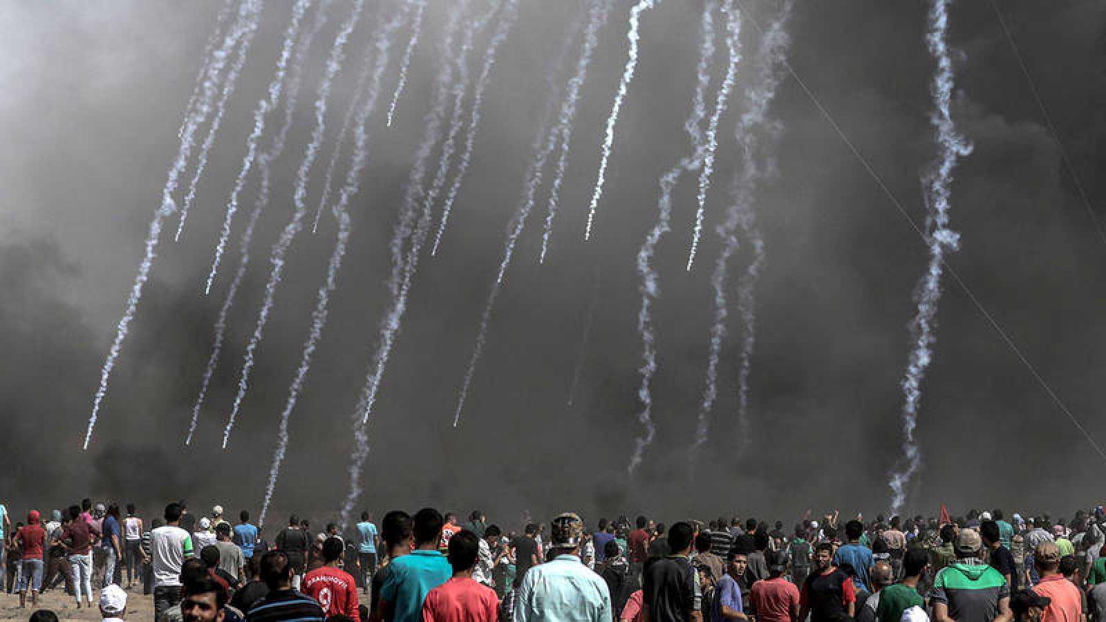 Manifestantes palestinos observan el impacto de gas lacrimógeno israelí en Gaza
