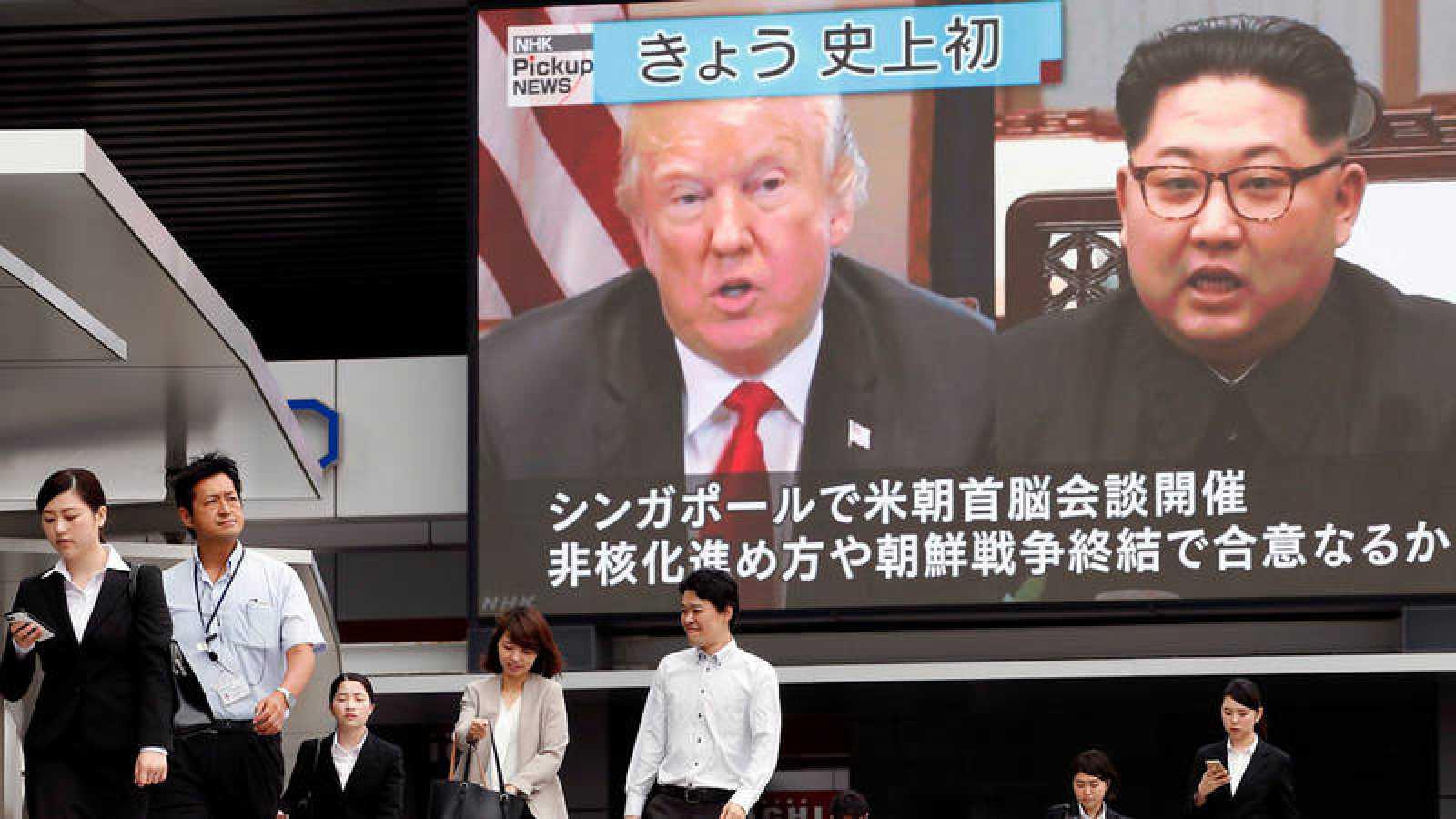 Una persona pasa frente a una gran pantalla con la transmisión de la cumbre entre el líder norcoreano, Kim Jong-un y el presidente estadounidense, Donald J. Trump