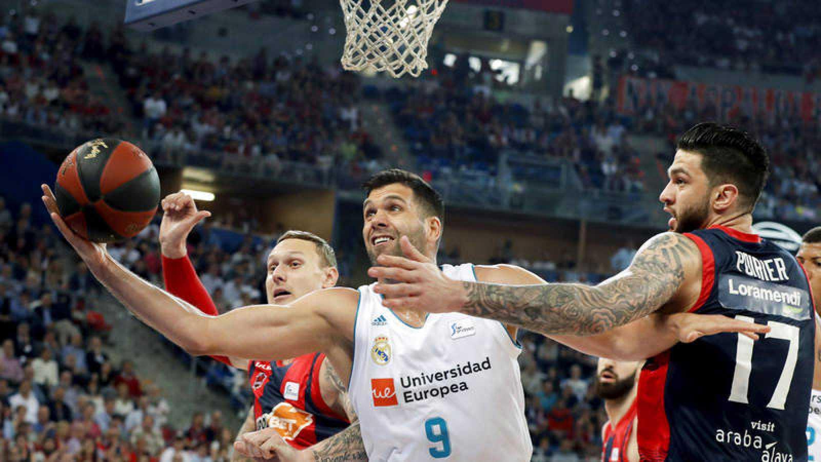 El pívot del Real Madrid Felipe Reyes lucha el balón con los jugadores del Baskonia Janis Timma y Vincent Poirier