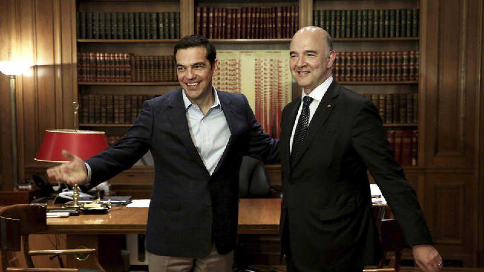 El primer ministro griego, Alexis Tsipras, conversa con el comisario europeo de Asuntos Económicos y Financieros, Pierre Moscovici, durante un encuentro en Atenas