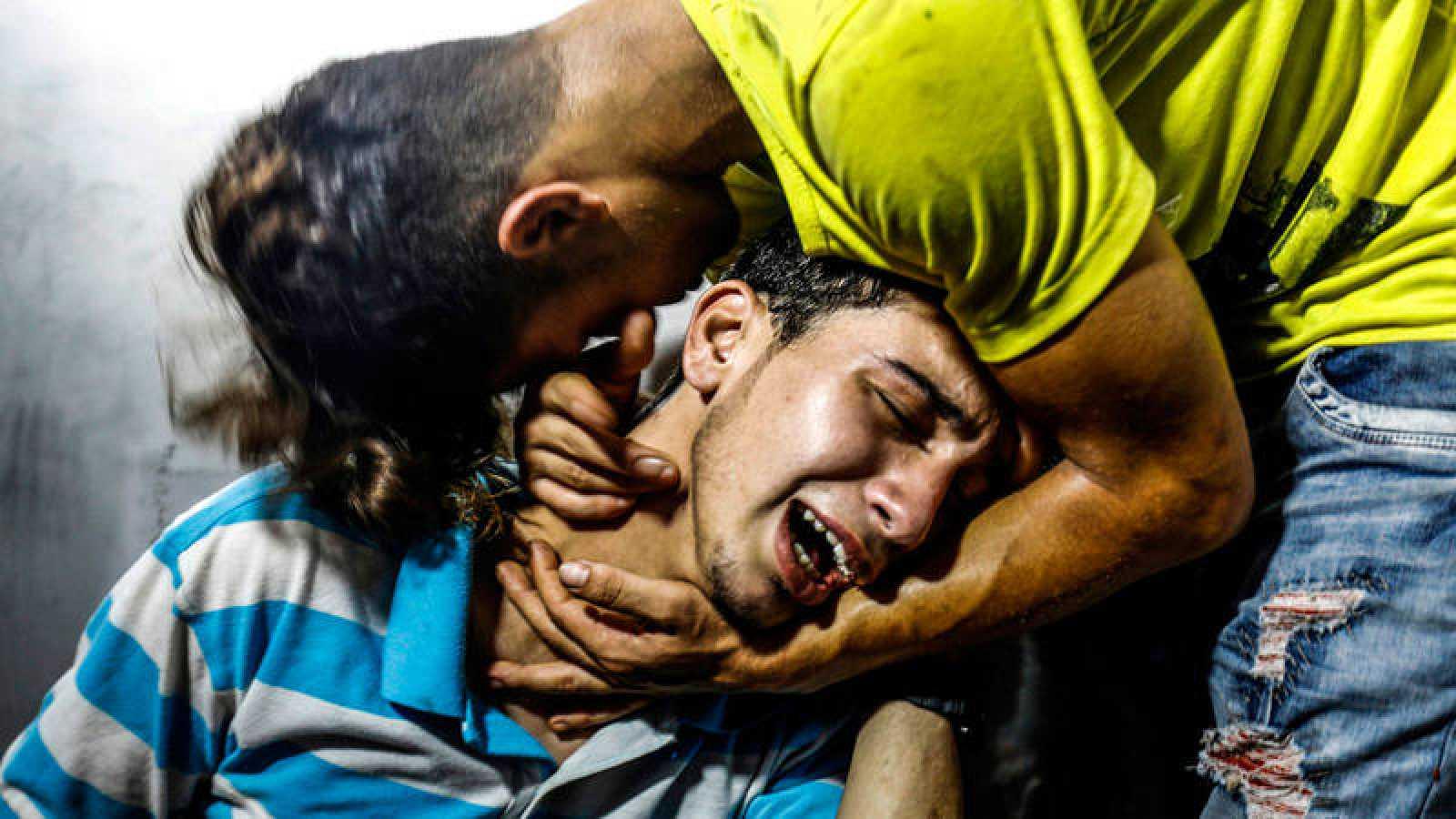 Jóvenes palestinos lloran en la morgue del hospital de Al-Shifa la muerte de los dos adolescentes palestinos