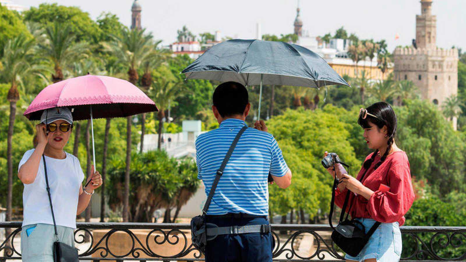 Turistas se protegen del sol por el intenso calor.