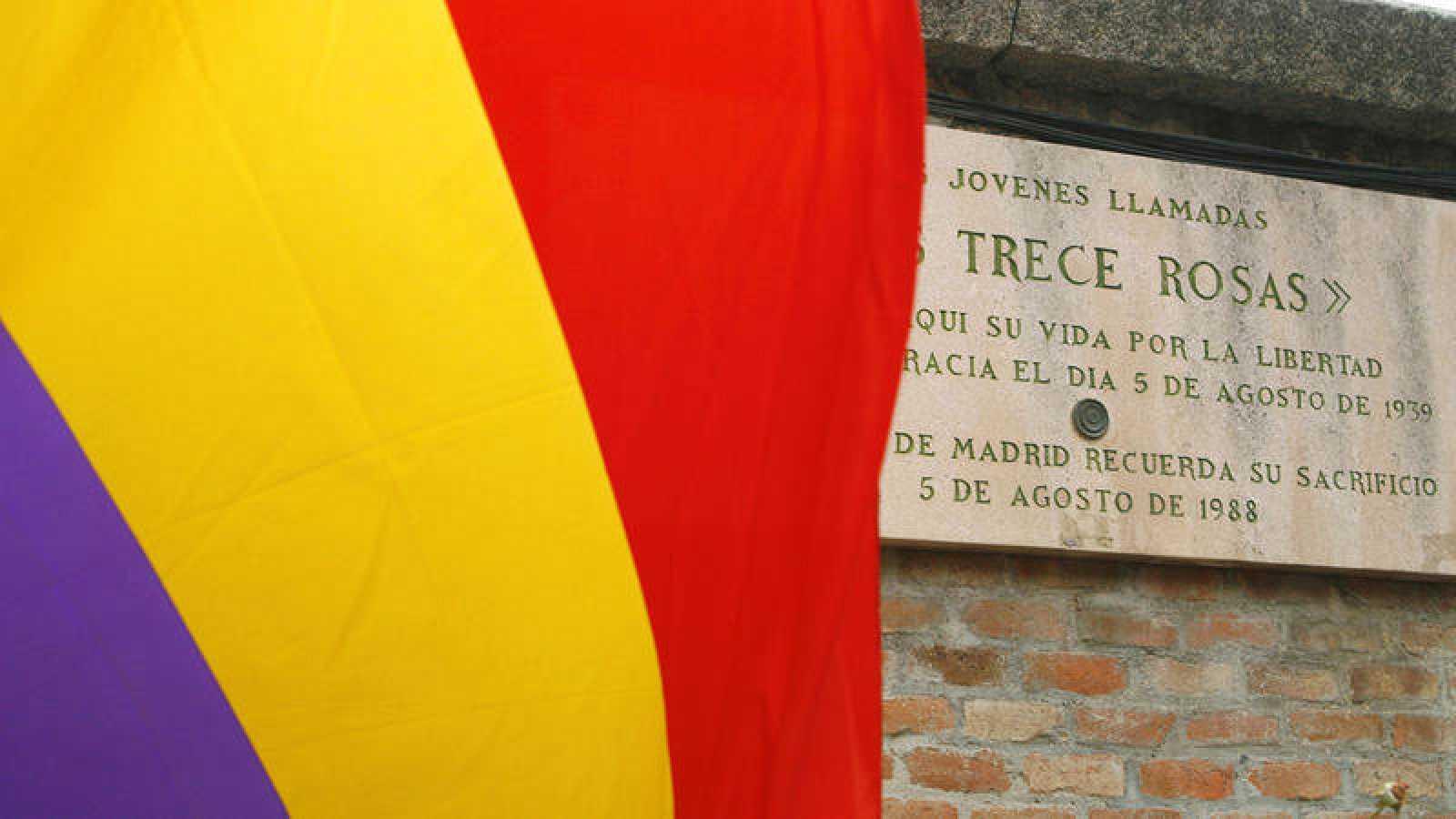 Una bandera republicana ondea junto a la placa que recuerda en el cementerio de la Almudena a las Trece Rosas