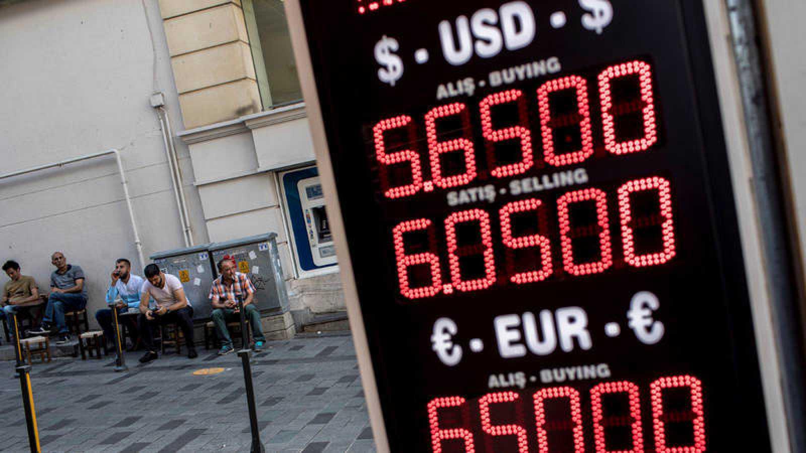 Varios hombres descansan frente a una oficina de cambio de divisas en una calle comercial en Estambul
