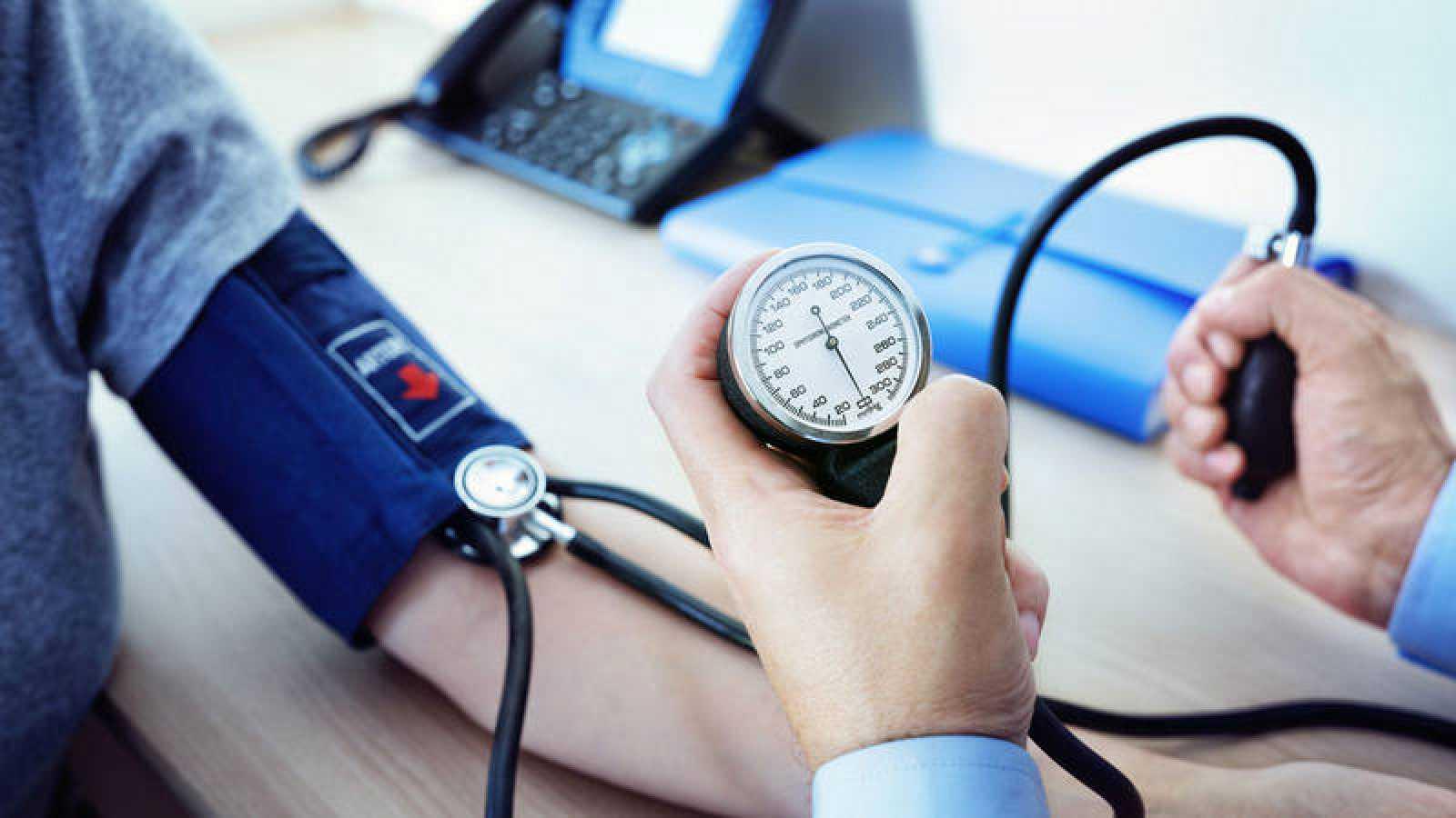 Un médico toma la tensión arterial a un paciente