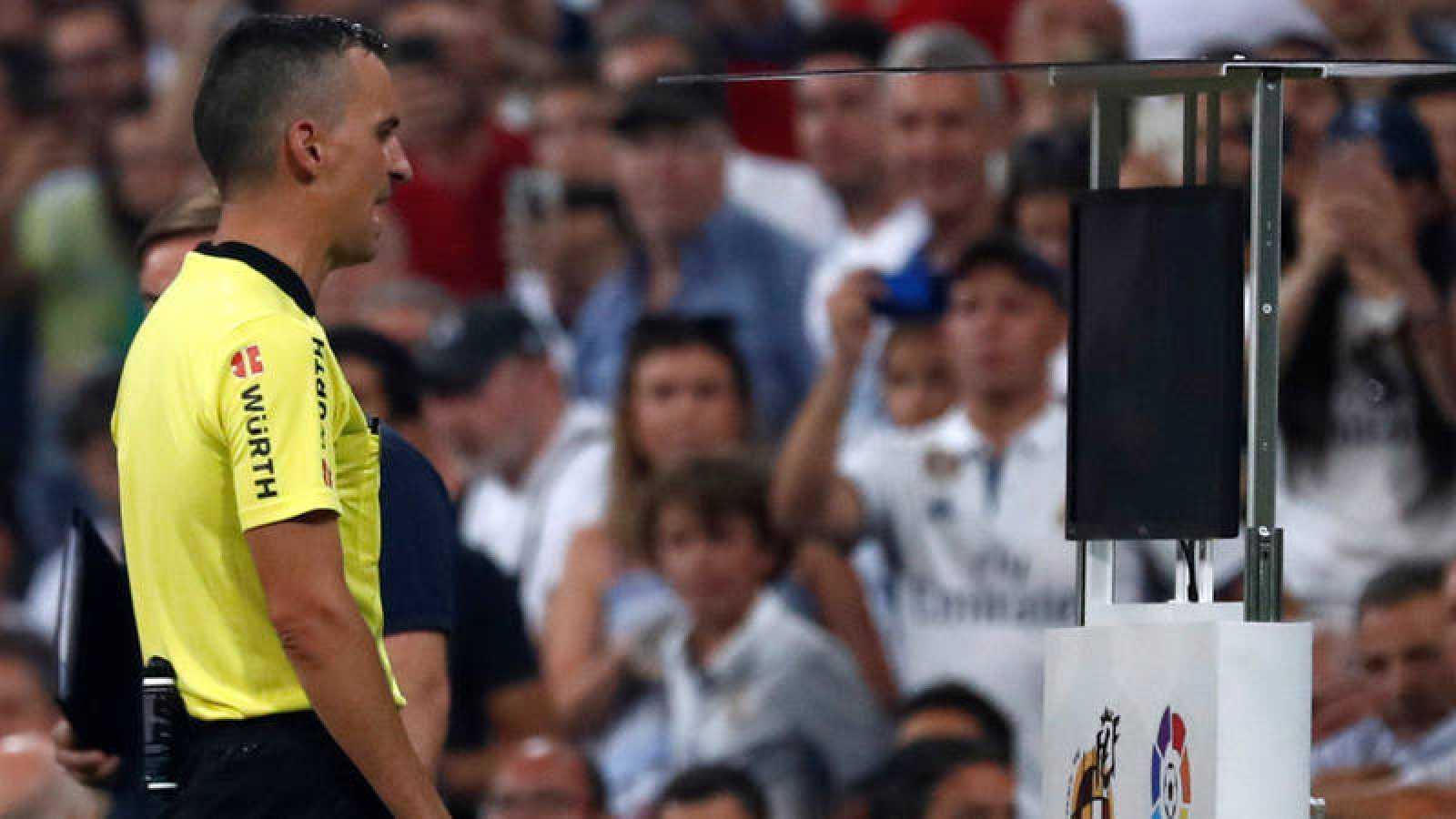 El árbitro Jaime Latre consulta el VAR en el Bernabéu.