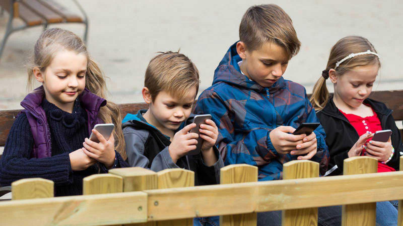 Un grupo de niños utiliza su teléfono móvil