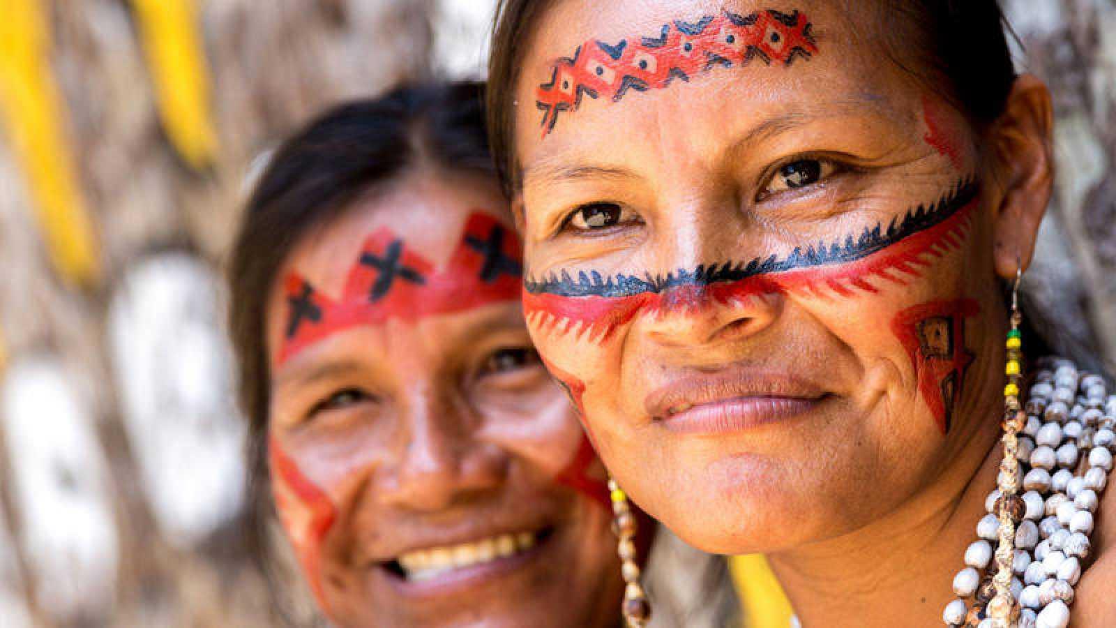Dos mujeres indígenas sonríen con la cara pintada al modo tradicional.