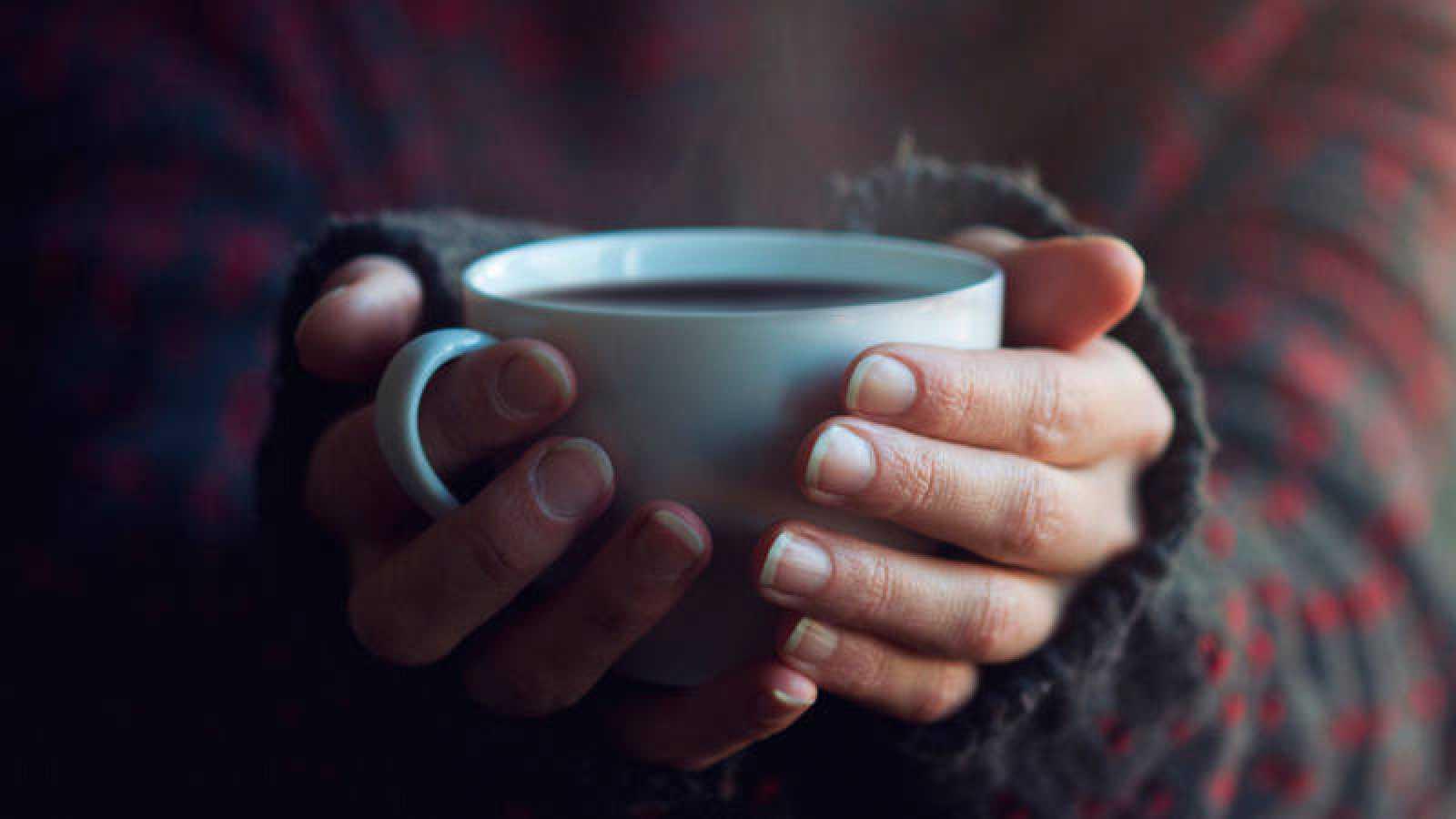 Una mujer sostiene una taza caliente con sus manos