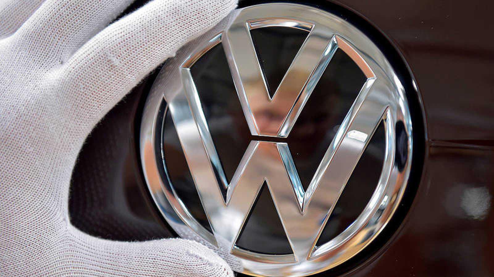 Un mecánico coloca el logotipo de Volkswagen en un modelo eléctrico e-Golf en Dresde, Alemania